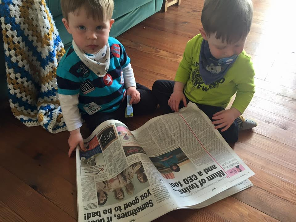 Checking Out Their Super Mum On The Paper