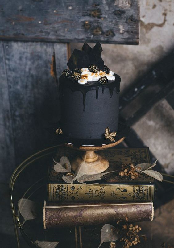 07-a-matte-black-wedding-cake-with-black-drip-cream-gilded-blackberries-and-chocolate-on-top