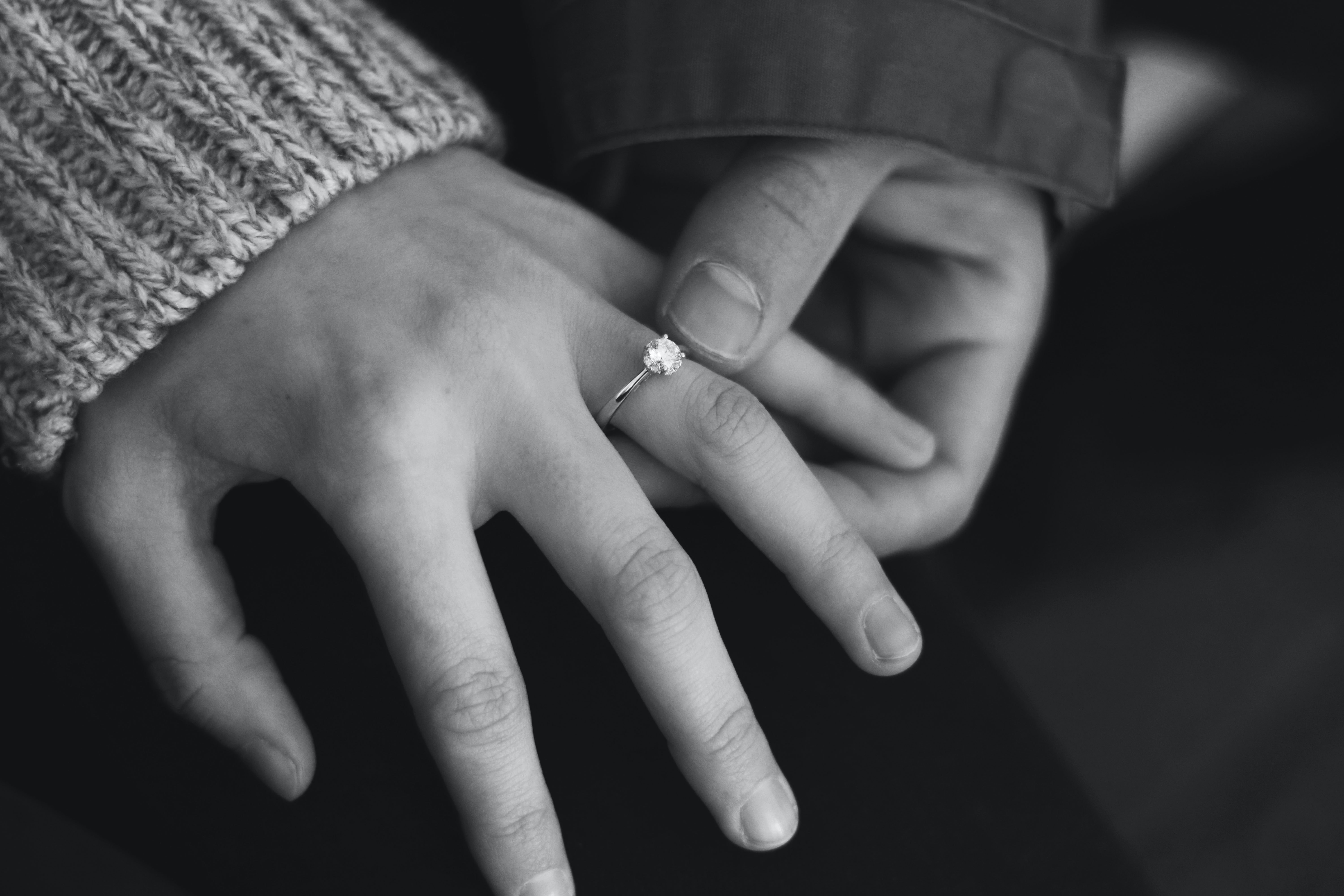 a female hand with an engagement ring is held by another hand