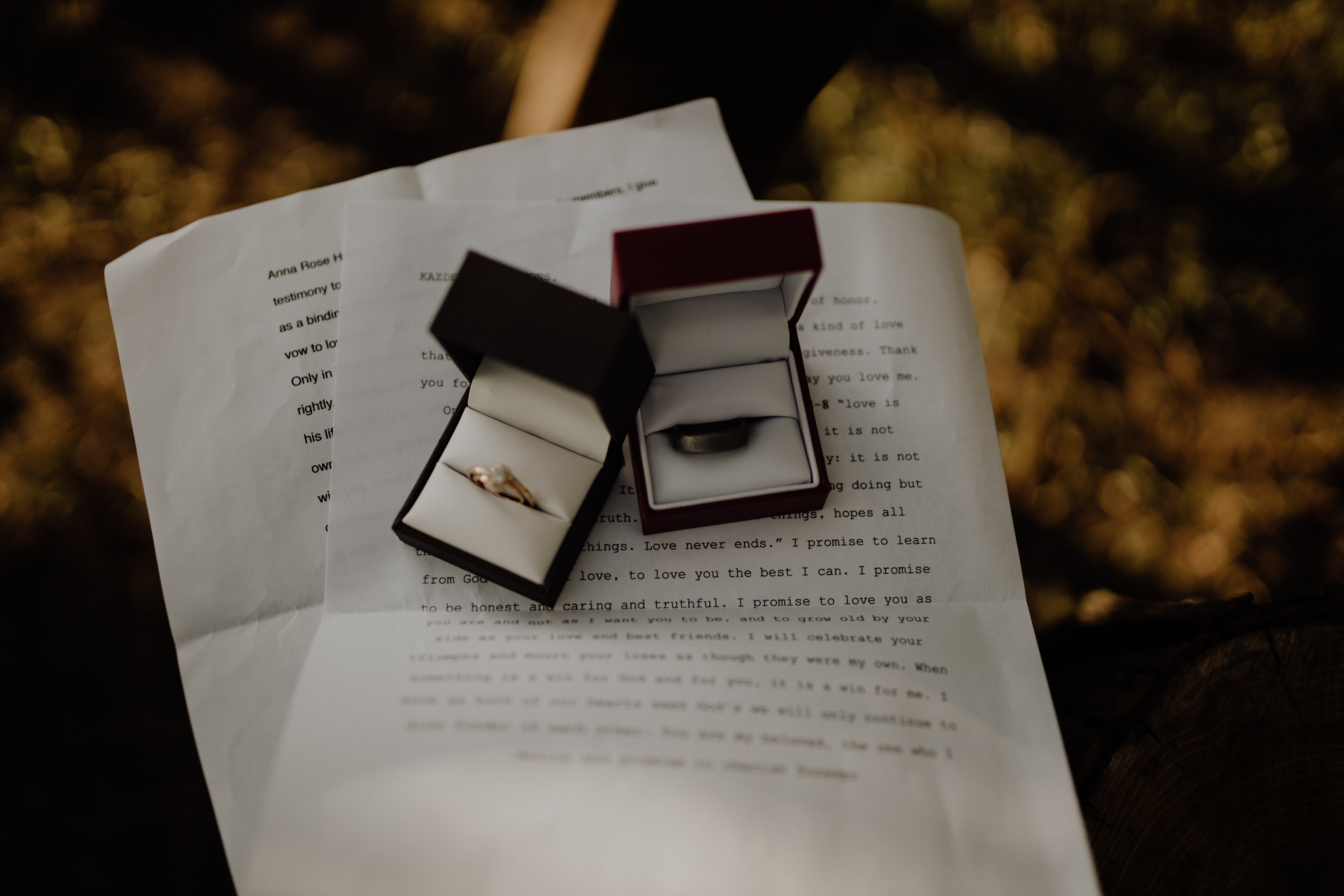 Two boxes with wedding rings sitting on sheets of paper with typed text