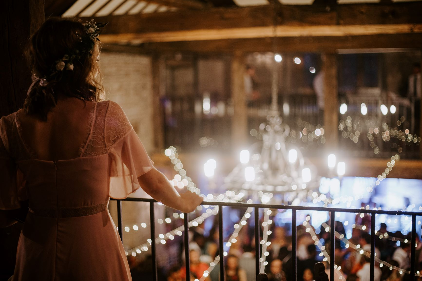 A bride is standing on a balcony looking away from the camera over a room laid out for a reception